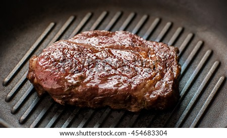 Meat on frying pan. Dark-colored piece of meat. Ribey steak cooked at restaurant. Delicious juicy beef. - stock photo