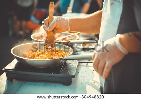 Meat on frying pan. Street food and outdoor cooking concept Toned picture