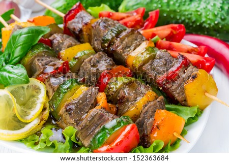 Meat on skewers with vegetables on salad leaves - stock photo