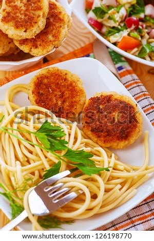 Meat patties and pasta in white plate on checkered napkin. - stock photo