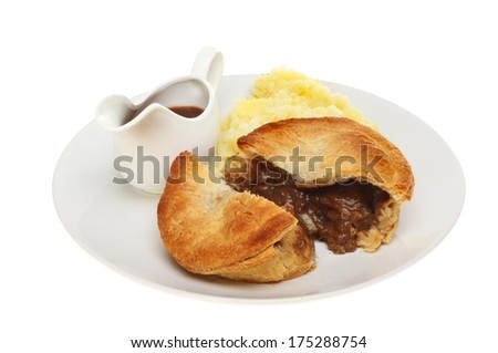 Meat pie mashed potato and gravy in a jug on a plate isolated against white - stock photo