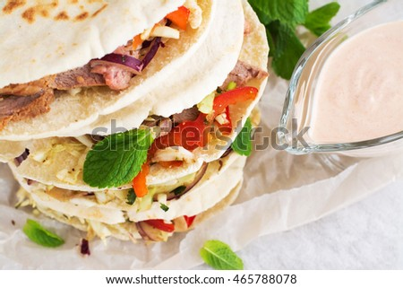Meat pita bread with yogurt sauce and mint leaves. Selective focus