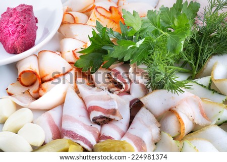 Meat plate of 4 varieties of sliced meats, pickled cucumbers and garlic, parsley and dill served with horseradish sauce and mustard. - stock photo