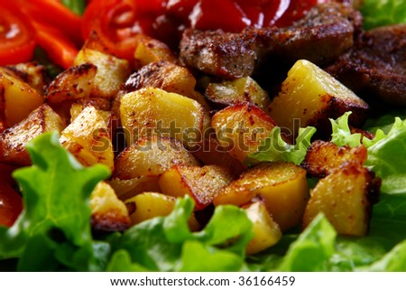 Meat plate with potatoes and sauce - stock photo