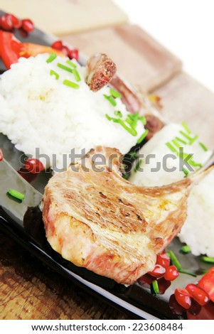 meat portion: barbecued ribs served with rice and tomatoes on black over wood - stock photo