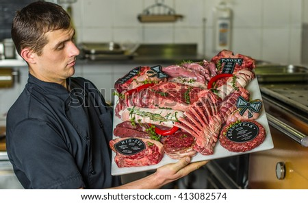 Meat raw different . Meat board in the hands of the chef. Cook offers steaks to choose from. Close-up in the kitchen .