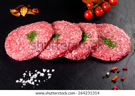 Meat. Raw meat. burger steak on black background with herbs and tomato - stock photo
