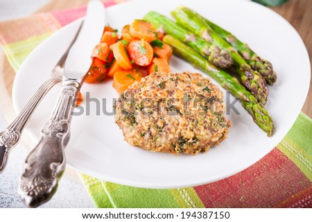 Meat rissole with glazed carrots, asparagus on the plate  - stock photo