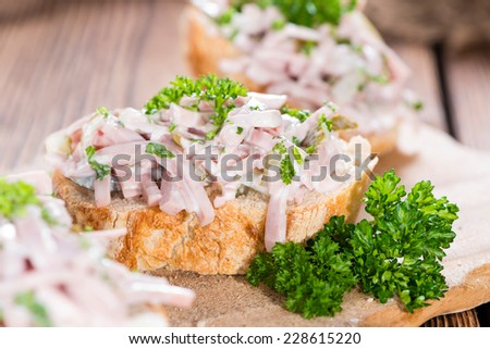 Meat Salad with mayonnaise on a piece of bread (close-up shot)