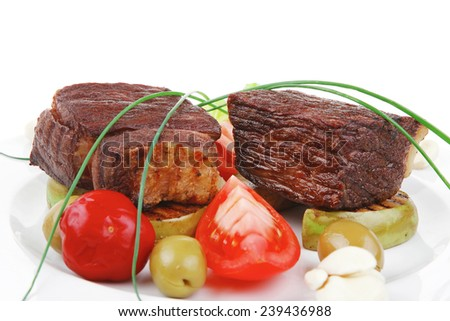 meat savory : beef fillet mignon grilled and garnished with baked apples and tomatoes on white plate isolated over white background