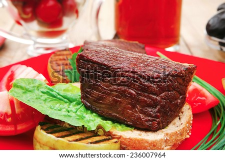meat savory : beef fillet mignon grilled and garnished with vegetables , juice and olives on red plate over wooden table - stock photo