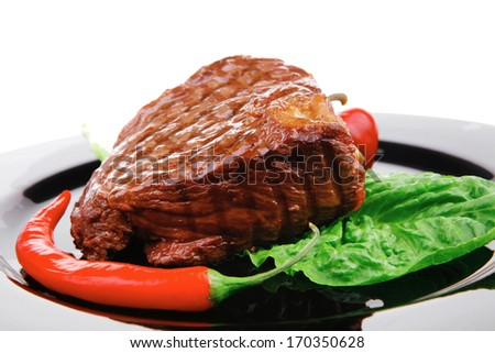 meat savory : beef grilled and garnished with green lettuce and red chili hot pepper on black dish isolated over white background - stock photo