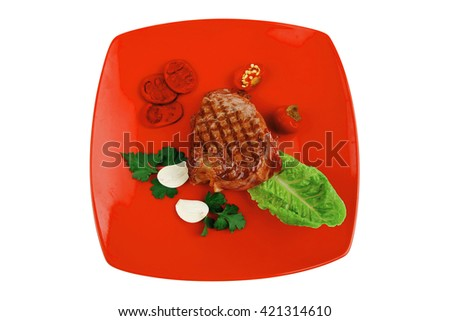 meat savory : beef grilled and garnished with green lettuce and red chili hot pepper on red plate isolated over white background - stock photo