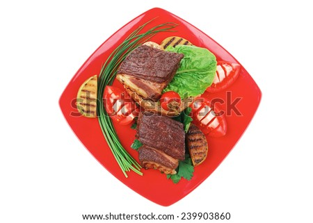 meat savory : beef roasted and garnished with baked apples, raw tomatoes, green chives and pepper, over bread slice on red plate isolated over white background - stock photo