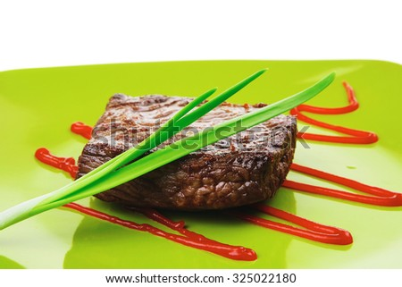 meat savory : grilled beef fillet mignon served on green plate isolated over white background with chives and ketchup - stock photo