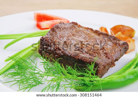 meat savory : grilled beef fillet mignon served on white plate over wooden table with chili pepper and tomatoes - stock photo