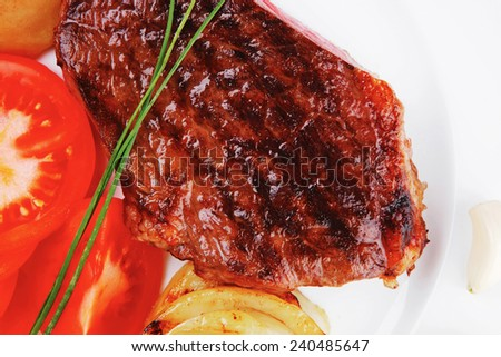 meat savory : grilled beef fillet steak on white plate with tomatoes , potatoes and chives isolated over white background