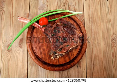 meat savory : grilled beef ribs served with green chives and cherry tomato over wood - stock photo