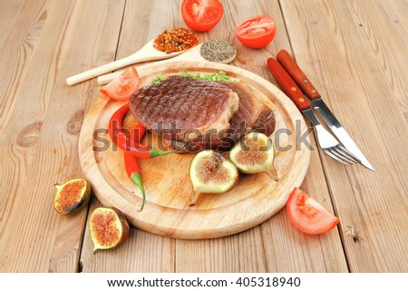 meat savory : grilled beefsteak served with hot cayenne peppers green stuff sweet figs and cutlery on wood plate over wooden table - stock photo