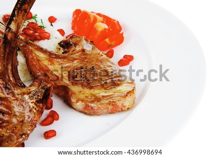 meat savory: roast veal ribs with rice garnish and pomegranate seeds over white background - stock photo