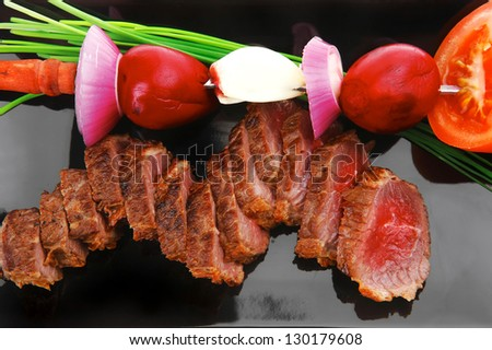 meat savory : roasted bbq meat served on black plate with vegetables on spit isolated on white background - stock photo