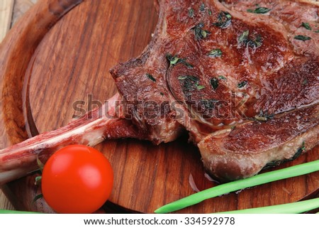 meat savory : roasted beef ribs served with green chives and cherry tomato over wood - stock photo