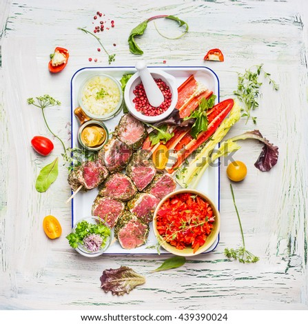 Meat skewers with fresh cutting vegetables and seasoning on enamel  plate . Meat skewers  for grill or cooking, preparation on light rustic background, top view - stock photo