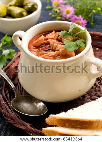 Meat soup with parsley in pot. Selective focus - stock photo
