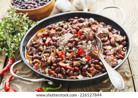 Meat stew with red beans and chili pepper on the table  - stock photo