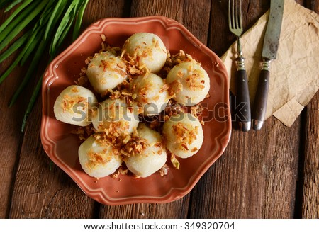 Meat stuffed potato dumplings with fried onion  and greaves on top - stock photo