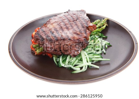 meat table : grilled beef fillet with asparagus and tomatoes served on dish isolated over white - stock photo