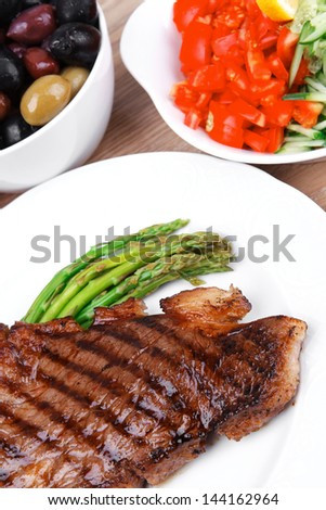 meat table : grilled beef fillet with asparagus , pasta portion , tomatoes and several kinds of olives served on white dish over light wood