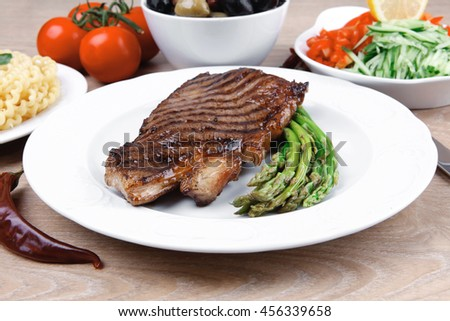 meat table : grilled beef fillet with asparagus , pasta portion , tomatoes and several kinds of olives served on white dish over light wood - stock photo