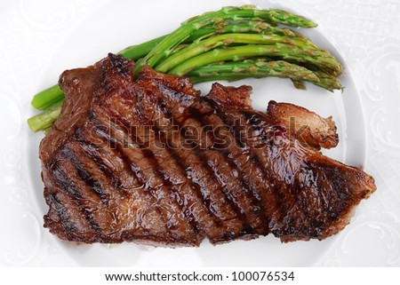 meat table : grilled beef fillet with asparagus served on white dish over light wood