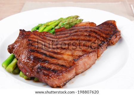meat table : rare medium roast beef fillet with asparagus served on white plate with cutlery over wooden table - stock photo