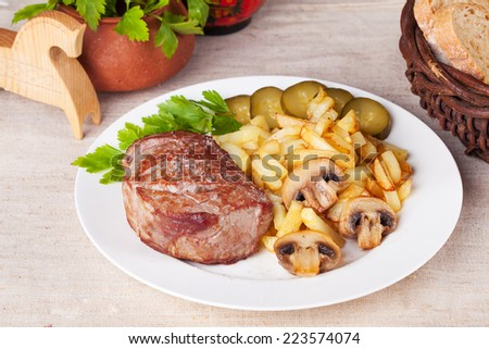 meat with french fries and pickles in a still life rustic, rural, county
