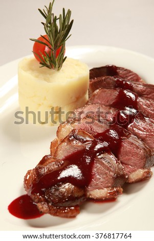 Meat with tomato sauce garnished with potato