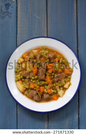meat with vegetables in dish on blue background