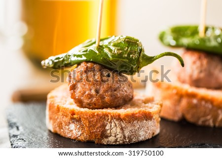 Meatball tapas with green pepper on a slate dish. - stock photo