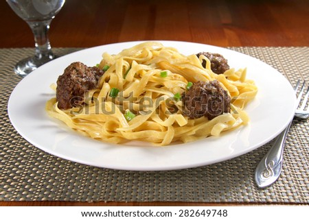 Meatballs and pasta on a white plate, shallow focus - stock photo