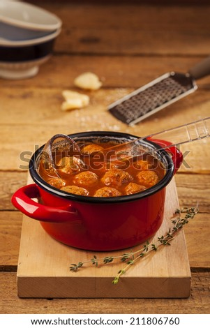 Meatballs closeup in a red casserole on wooden background - stock photo