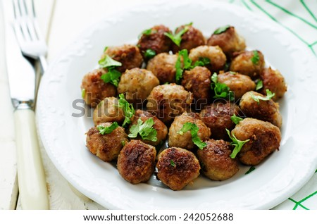 meatballs grilled with parsley on a white wood background. tinting. selective focus