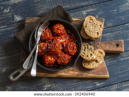 Meatballs in a pan on rustic wooden board - stock photo