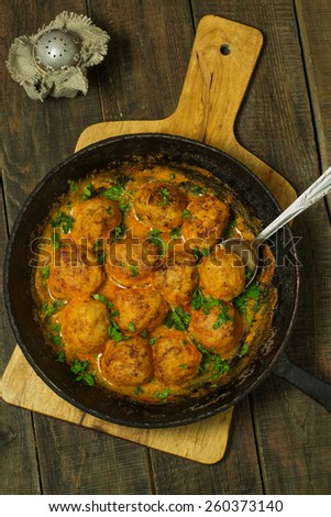 Meatballs in sauce in a pan and a wooden background. Vintage style - stock photo