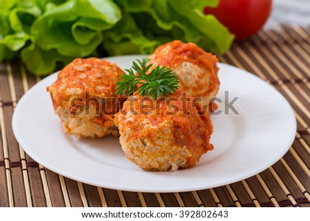 Meatballs in tomato sauce on a white plate