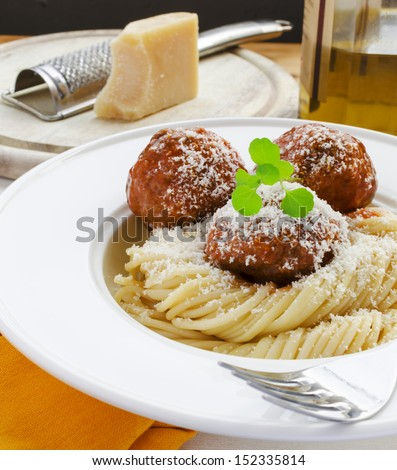 Meatballs in tomato sauce with pasta, watercress and parmesan cheese