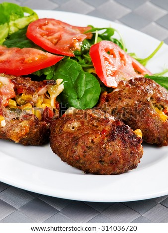 Meatballs with corn and cheese. Served with salad. Tilted view. Shot from above.