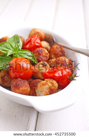 meatballs with tomato in a white dish on a white background.