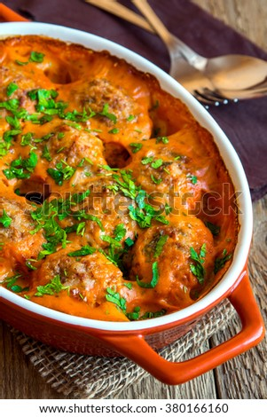 Meatballs with tomato sauce and parsley in baking dish over rustic wooden background