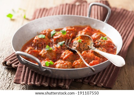 meatballs with tomato sauce in pan with spoon  - stock photo